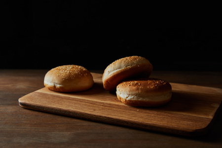 Fresh delicious buns with sesame on wooden chopping board isolated on black background