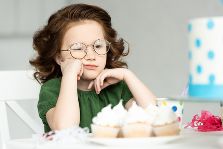 Adorable bored preteen propping chin while sitting at table with cupcakes Фото со стока - 120874935