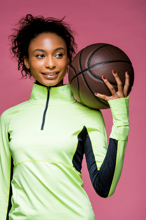beautiful smiling african american sportswoman holding basketball isolated on pink Reklamní fotografie