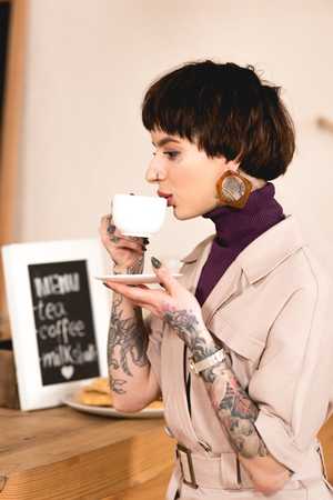 beautiful businesswoman drinking coffee at bar counter in coffee shop