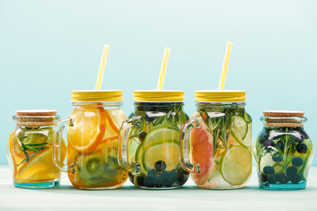 fresh detox drinks with berries, fruits and vegetables in jars with straws isolated on blue