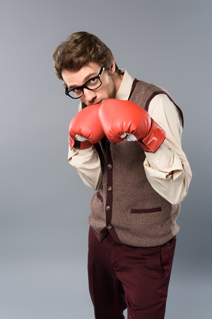 serious man in glasses and boxing gloves on grey background
