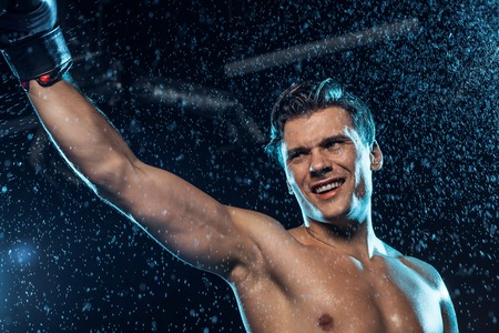Smiling boxer standing with hand up under water drops on black