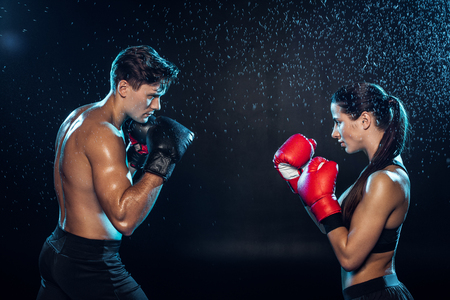 Side view of two boxers in boxing gloves training together under water drops on black
