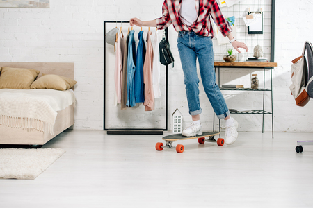 Cropped view of teenager in jeans and checkered shirt standing on longboard in bedroom