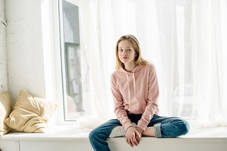 Nachdenkliches Teenager-Kind in Jeans, das auf der Fensterbank sitzt und wegschaut Standard-Bild