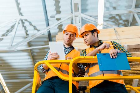 Trabajadores multiculturales reflexivos con tableta digital mientras está de pie en el elevador de tijera en el almacén Foto de archivo