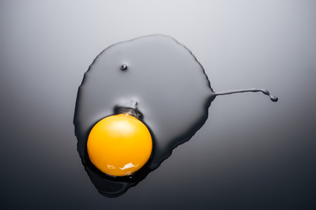 close up of raw smashed egg with yolk and protein on black background