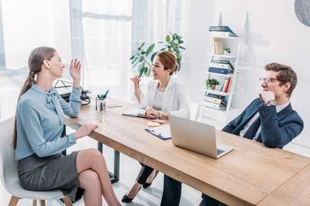 attractive employee gesturing while taking on job interview with recruiters