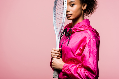 Beautiful African American sportswoman looking at camera and holding tennis racket isolated on pink with copy space 写真素材