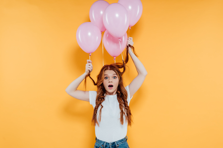 surprised redhead girl with balloons tied to hair looking at camera and posing isolated on yellow Фото со стока