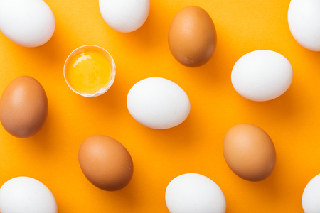 Top view of whole white and brown fresh chicken eggs with smashed one on bright orange background