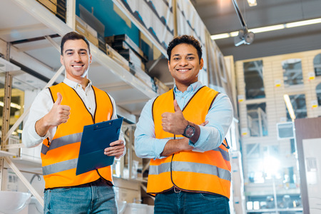 Cheerful multicultural warehouse workers showing thumbs up and looking at camera Archivio Fotografico