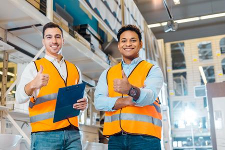 Trabajadores alegres del almacén multicultural mostrando los pulgares hacia arriba y mirando a la cámara Foto de archivo