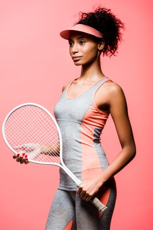 beautiful african american sportswoman in sun visor holding tennis racket isolated on coral