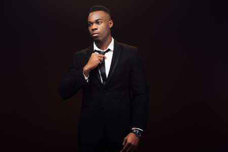 Handsome fashionable African American man in suit adjusting tie isolated on black background