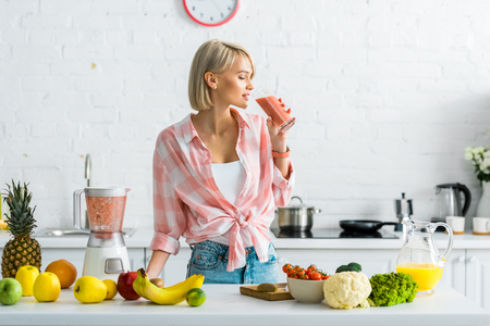 Attractive blonde woman drinking tasty smoothie near ingredients in kitchen Stockfoto - 120874998