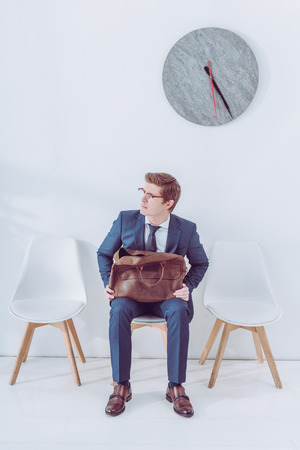 Worried man in glasses holding briefcase while waiting job interview
