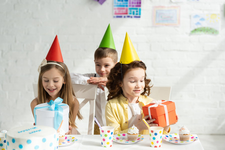 adorable kids in party caps sitting at table with gift boxes during birthday party at home