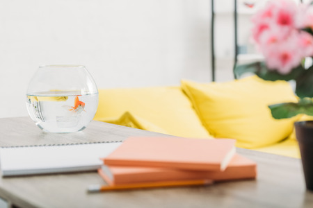 Selective focus of aquarium with gold fish on wooden table near books