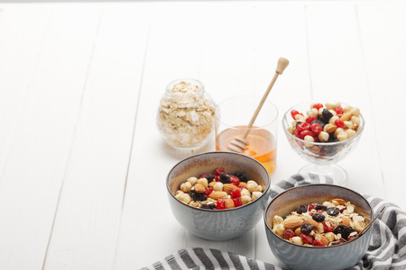 Bowls with muesli, dried berries and nuts served for breakfast with honey on white wooden table with copy space