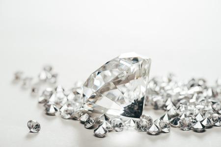 Selektiver Fokus des funkelnden reinen großen Diamanten unter den kleinen auf weißem Hintergrund Standard-Bild