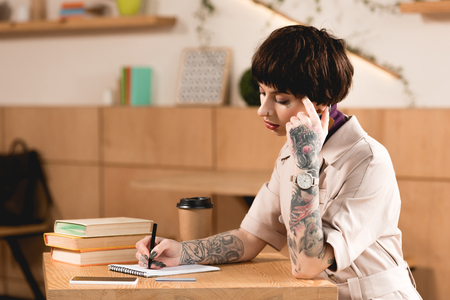Pretty businesswoman writing in notebook while sitting at table near books and paper cup Stock Photo
