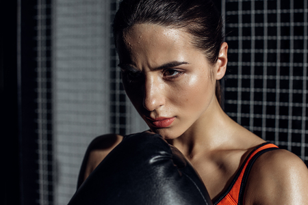 Concentrated pretty boxer in black boxing glove looking away 写真素材