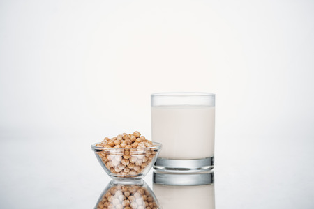 Chickpea vegan milk in glass near bowl with beans on grey background