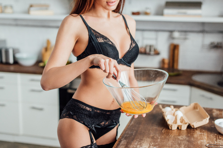 Cropped view of sexy woman in black lingerie whipping eggs with whisk in kitchen
