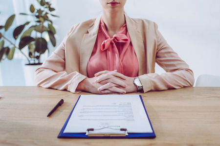 cropped view of recruiter sitting with clenched hands near clipboard in office Imagens