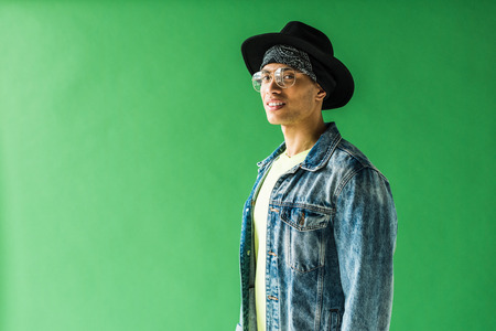 stylish mixed race man looking at camera and smiling on green screen with copy space Stock Photo