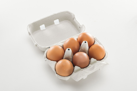 raw brown chicken eggs in carton box on white background