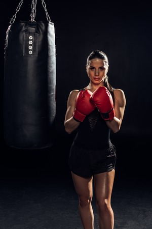 Front view of boxer in red boxing gloves standing near punching bag on black