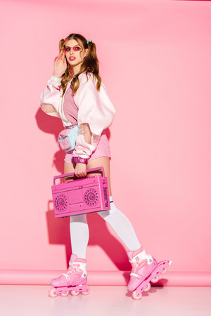stylish girl touching sunglasses and holding retro boombox while standing in roller-skates on pink