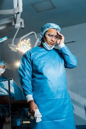 Selektiver Fokus des Arztes in Uniform und medizinischer Maske, der im Operationssaal wegschaut