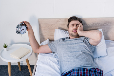 overslept man with closed eyes holding alarm clock while laying on bed Stock Photo