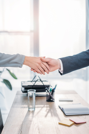 cropped view of recruiter and employee shaking hands in modern office