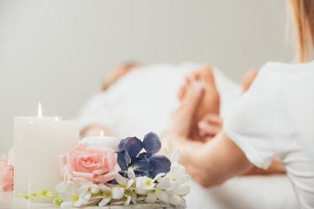 Vista recortada del masajista haciendo masaje de pies a mujer adulta en spa
