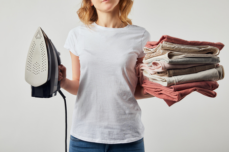 Partial woman in t-shirt holding iron and folded ironed clothes isolated on grey Stock fotó