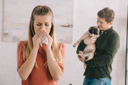 selective focus of blonde girl allergic to dog sneezing in white tissue near man with cute pet Фото со стока