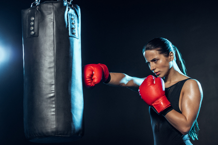 Tired boxer in red boxing gloves training with punching bag on black background