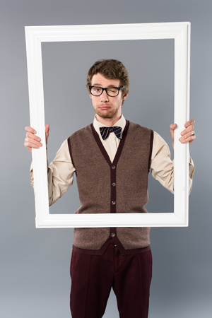 man in glasses winking and holding white frame on grey background 版權商用圖片 - 120972728