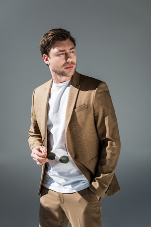 handsome man in beige suite holding sunglasses and looking away on grey Фото со стока