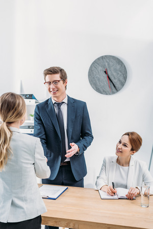 Cheerful recruiter in glasses shaking hands with woman on job interview Imagens