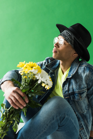 Stylish mixed race man in denim posing with flowers on green screen background Stock Photo