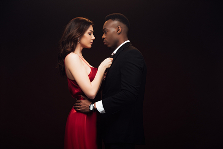 Beautiful woman in red dress posing with African American man in suit isolated on black with copy space