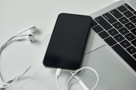 Laptop with black keyboard, smartphone with blank screen and earphones on white surface Imagens
