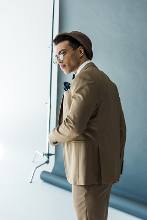 Fashionable mixed race man in suit and hat posing on grey background