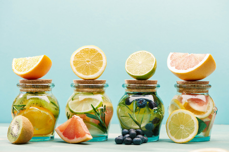Fresh detox drinks in jars with ingredients isolated on blue background